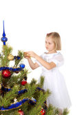Nice girl decorates a Christmas tree — Stock Photo
