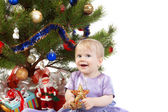 Baby girl under the Christmas tree — Stockfoto