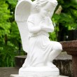 Statue of an angel in prayer on the marble slabs - Stock Photo