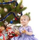 Happy baby girl make a wish under the Christmas tree — Stock Photo