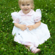 Young beautiful baby girl lays on a grass — Stock Photo