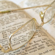 Open book with gold color glasses - Stock Photo