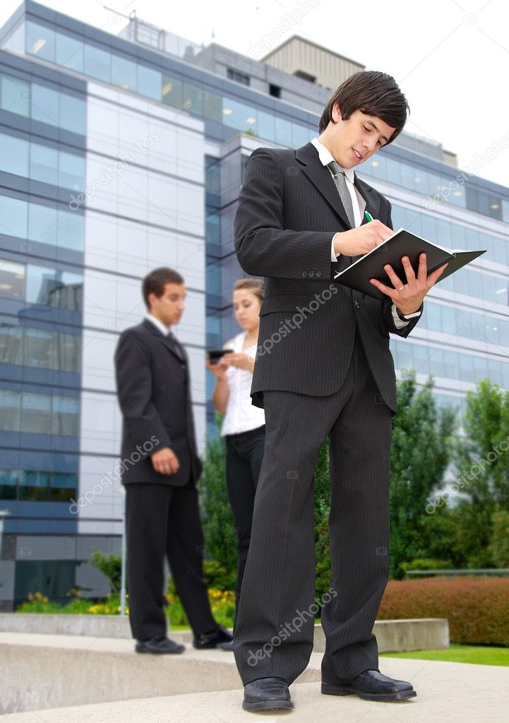 Business woman and two men on a background of office buildings — Stock Photo #2721007