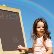 Girl drawing on blackboard — Stock Photo