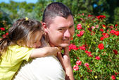 Little girl hugging her father in the park — Stock Photo
