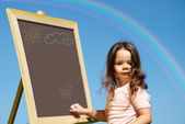 Girl drawing on blackboard — Stock Photo
