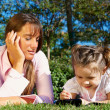 Mother and daughter lying in a park — Stock Photo #2958299
