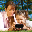 Stock Photo: Mother and daughter with mobile phone