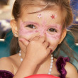 Beautiful little girl with painted face with paints — Stock Photo