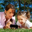 Stock Photo: Mother and daughter lying in park
