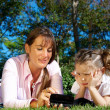Stock Photo: Mother and daughter lying in a park