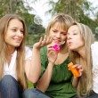 Stock Photo: Girls inflating soap-bubbles