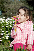 Licking lollipop candy — Stock Photo