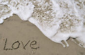 Love written in the sand with wave — Stock Photo