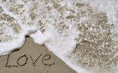 Liefde geschreven in het zand met golf — Stockfoto
