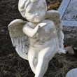 Foto Stock: Gravesite - Cherub blowing kiss - background