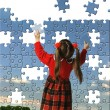 The girl assemble big puzzle — Stock Photo #3311555