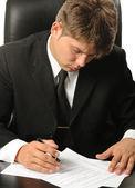 这名商人在签名前学习合同 — 图库照片