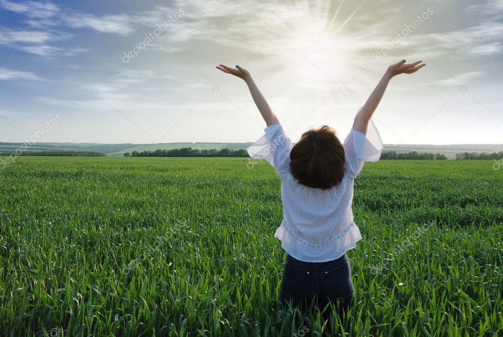 The girl on a field. The woman with the lifted hands to the sky on a green meadow  Stock Photo #3310887