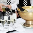 Stock Photo: Two waiters fill glasses of champagne