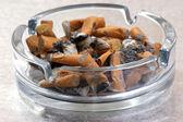 Cigarette in a glass ashtray — Stock Photo