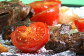 Organic tomato and meat on a grill — Stock Photo
