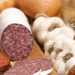Salami and some slices salami on a timber board - Stock Photo