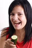 A young woman eating one organic cucumber — Stock Photo