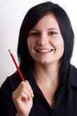 Young woman with a red pencil in her hand — Stock Photo