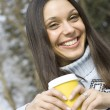 Foto Stock: Beautiful girl in a park drinking coffee