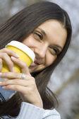 Vacker flicka i en park som dricker kaffe — Stockfoto