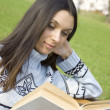 Foto Stock: Young womin park reading