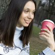 Beautiful girl in a park drinking coffee — Stock Photo