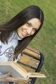 Young woman in a park with a book — Stock fotografie