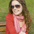 Beautiful girl in a park smiling. Thumb — Stock Photo
