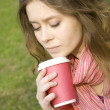 Female in a park drinking coffee - Stock Photo
