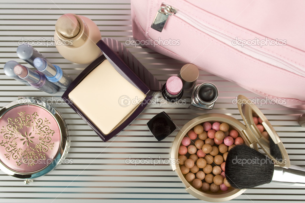 Cosmetics on the table. Basic colors pink and gold. Powder, skin cream, lipstick, handbag, vanity case, brush, eyeliner — Stock Photo #3069994
