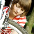 Stock Photo: Young girl mends bicycles