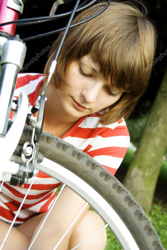 Young woman outdoors sitting next to the wheel of a bicycle. Breakage  Stock Photo #3457007