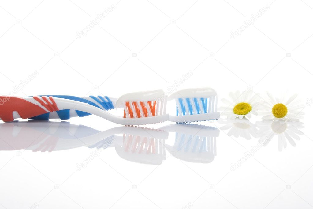 Two toothbrushes red and blue with toothpaste isolated on a white background and daisies. Metaphor sedation gum — Stock Photo #3467234