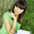 Stock Photo: Female in a park with a notebook