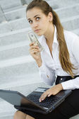 Business woman with money and a laptop — Stock Photo