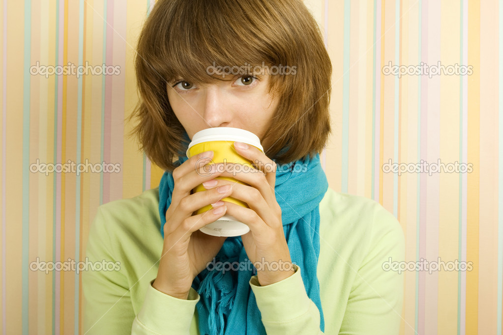 Young girl in a room drinking coffee / tea from a paper cup  Stock Photo #3769766