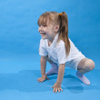 Small girl is posing as frog on blue — Stock Photo