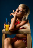 Cute blonde posing with a glass of juice — Stock Photo