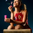 Cute blonde blowing soap bubbles — ストック写真