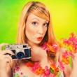 Pinup girl in a bikini holding a vintage camera — Stock Photo #3521385