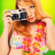 Pinup girl in a bikini holding a vintage camera — Stock Photo