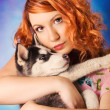 Royalty-Free Stock Photo: A redhead hugging a siberian husky puppy