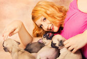 A redhead playing with puppies — Stock Photo